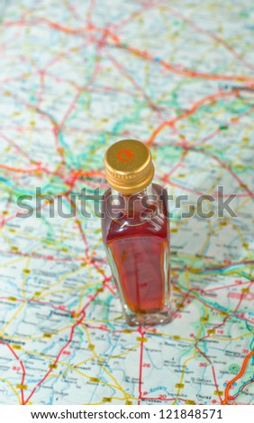 Bottle of whisky on a road map - stock photo