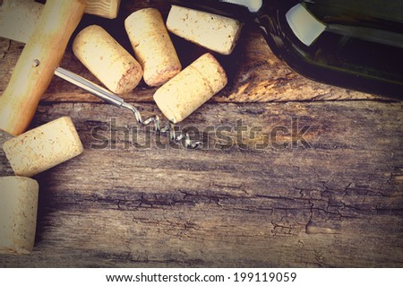 Bottle of white wine, corkscrew and corks on wooden table. Background - stock photo