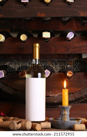 Bottle of white wine with blank label in wine cellar with used corks, bottle shelves and a burning candle