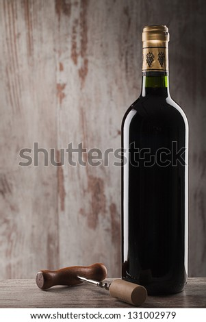 bottle of wine and corkscrew over wooden background - stock photo