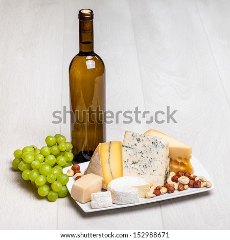 bottle of wine and different kinds of cheese on wooden background - cottage cheese, camambert, Parmigiano, Roquefort - stock photo