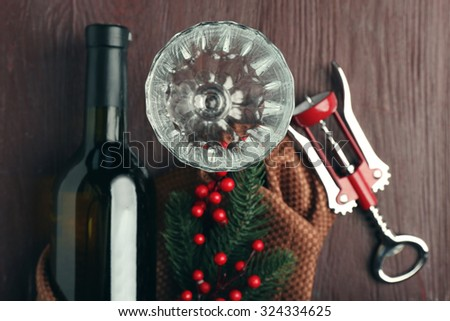 Bottle of wine and empty glass on wooden table - stock photo