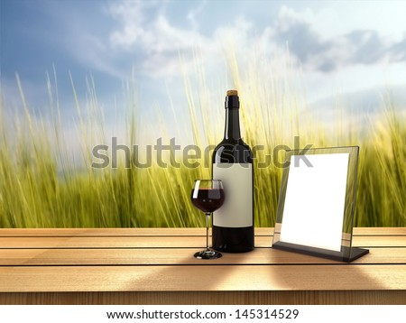 Bottle of wine and glass on sunny day - stock photo