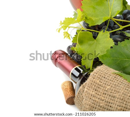 Bottle of wine and grapes, closeup on a white background