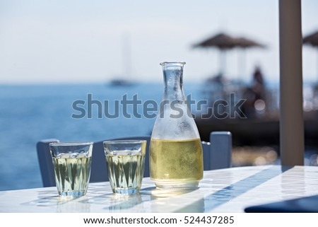 Bottle of wine and two glasses on the background of the sea