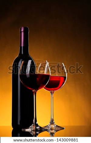bottle of wine and two glasses wine on yellow background - stock photo
