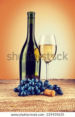 bottle of wine and wineglass with branch of grape on burlap instagram stile - stock photo