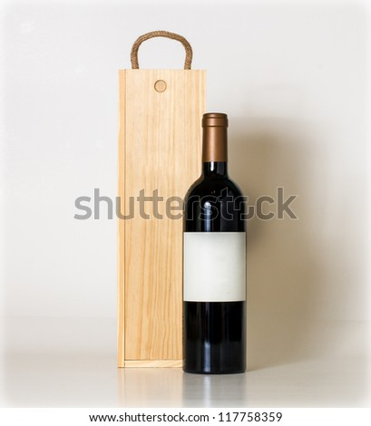 Bottle of wine and wooden box. - stock photo