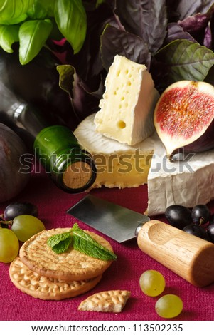 Bottle of wine, camembert, fig and crackers on a napkin.
