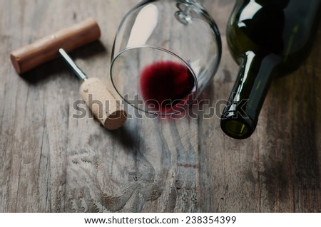 Bottle of wine, cork and corkscrew on wooden table - stock photo