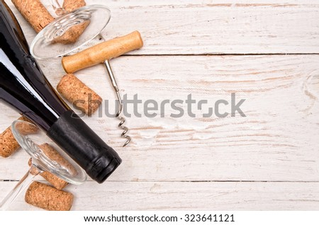 Bottle of  wine, corkscrew and corks on wooden table. Background - stock photo