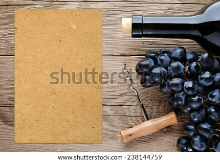 Bottle of wine, corkscrew, grape and blank paper - stock photo