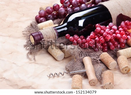 Bottle of wine, grapes and corks on old paper background - stock photo