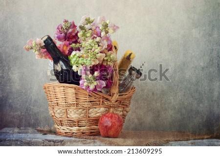 Bottle of wine in basket - stock photo
