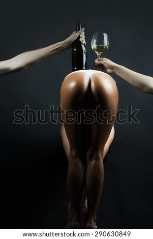Bottle of wine on a back of a hot posed woman - stock photo