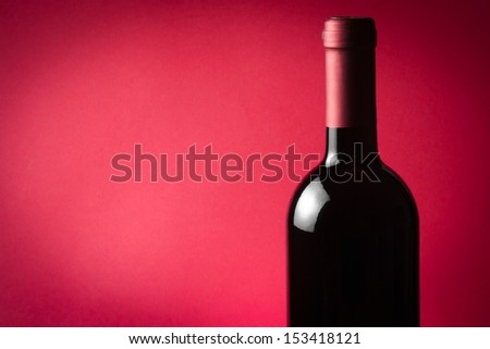 bottle of wine on red background - stock photo