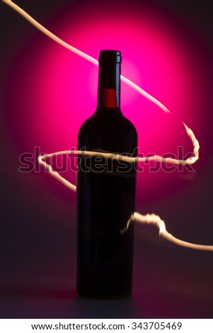 Bottle of wine on the pink background with flames - stock photo