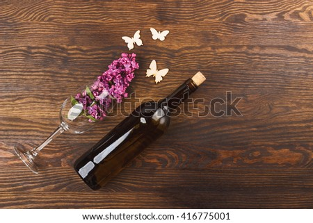 Bottle of wine, wineglass with lilacs and decorations on the wooden background - stock photo
