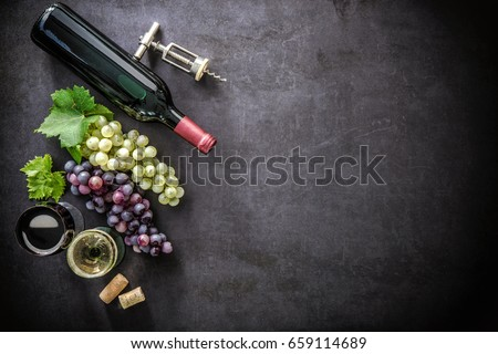 Bottle of wine, wineglasses, grapes and corks on dark background
