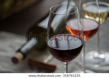 Bottle of wine  with three wineglasses of red, rose and white wine on brown wood textured table covered with canvas towel - stock photo