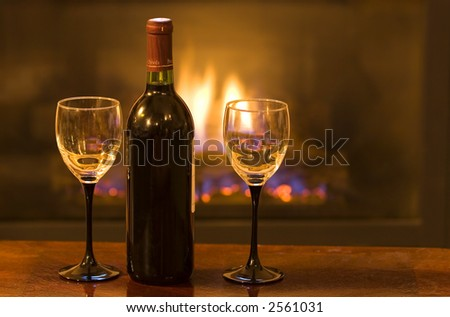 Bottle of wine with two empty glasses in front of a warm fire - stock photo