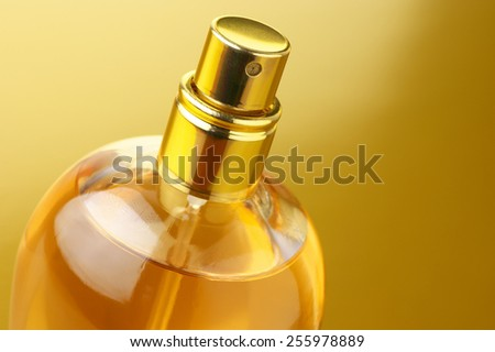 Bottle of woman perfume close-up on gold background. - stock photo