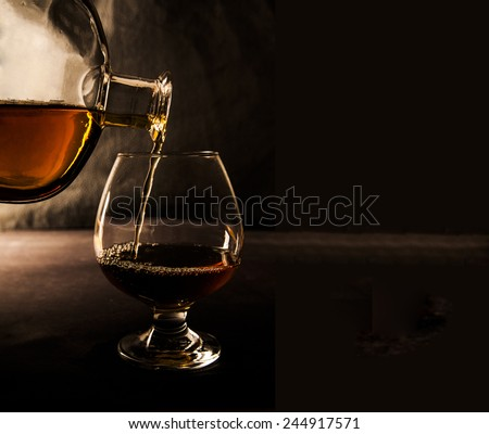 Bottle pour wineglass with scotch or cognac on dark background at night time Transparent glass stand on table on black wall texture background Empty space for inscription  - stock photo