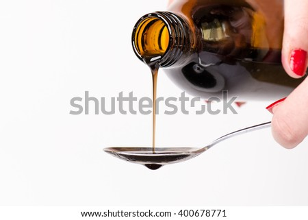 Bottle pouring a liquid on a spoon. Isolated on a white background. Pharmacy and healthy background.Cough and cold drug. Woman´s hand holding a bottle. - stock photo