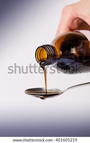 Bottle pouring a liquid on a spoon. Isolated on a white background. Pharmacy and healthy background. Medicine. Cough and cold drug.  - stock photo