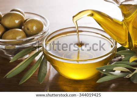 Bottle pouring virgin olive oil in a bowl close up. - stock photo