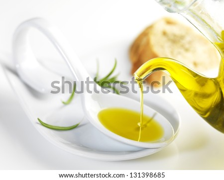 bottle pouring virgin olive oil in a porcelain spoon - stock photo