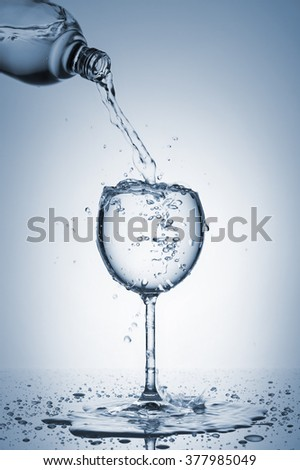 bottle pouring water in glass with splashes, on blue background - stock photo