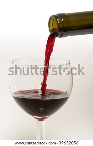 Bottle's neck and wine glass with streaming red wine isolated over white background