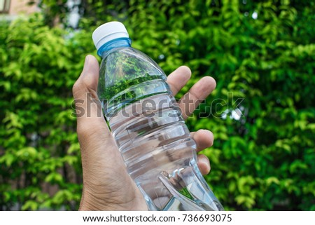 Bottle water made to plastic on sky and tree blurry background.Using wallpaper for package or product, refreshing image and copy space