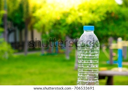 Bottle  water made to plastic on the wood and tree blurry bokeh background in garden. Using wallpaper for package or product and refreshing image.