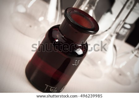 Bottle with a chemical poison in the background of laboratory glassware.
