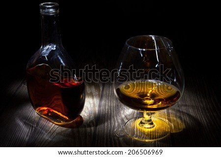Bottle with a glass of brandy on the table