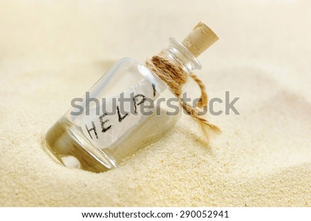 Bottle with a message on sand beach - stock photo