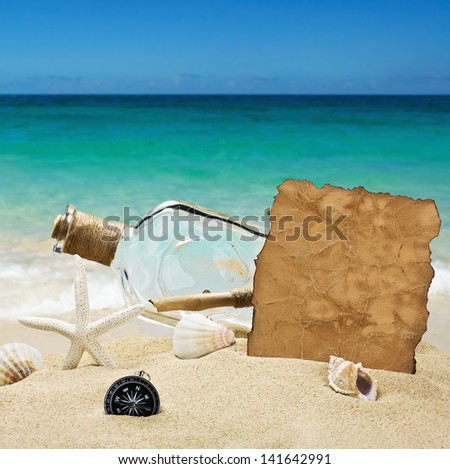 bottle with a note on the background of the sea beach - stock photo