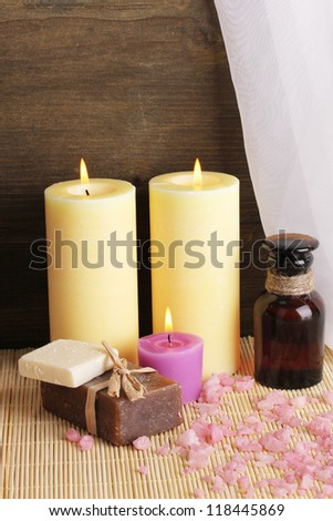 Bottle with aromatic oils with accessories for relaxation close-up on wooden table on wooden background - stock photo