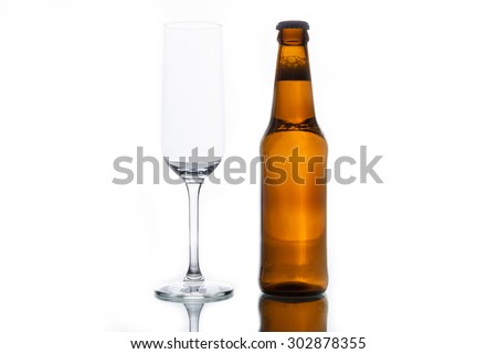 Bottle with beer and empty glass isolated on white background. - stock photo