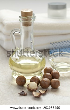 Bottle with cosmetic macadamia oil and nuts - stock photo