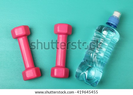 bottle with drinking water for training near pink dumbbell on turquoise background