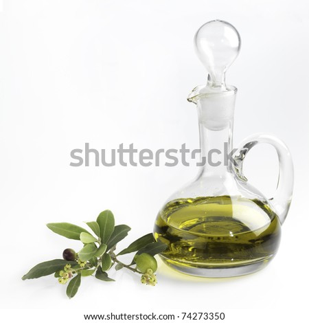 bottle with fine olive oil and a branch of an olive tree