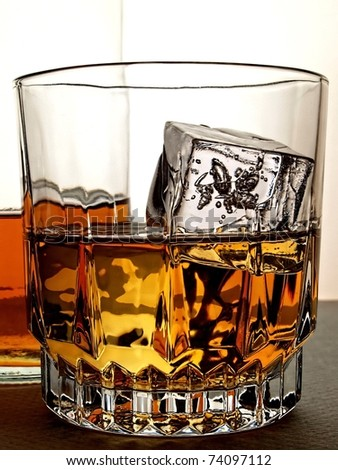 Bottle with glass of whiskey on ice cubes. - stock photo