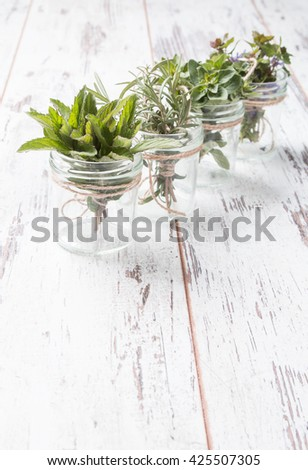 Bottle with herbs on white wooden background. Mint, thyme, balm and other medicinal herbs - stock photo