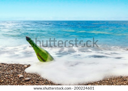 bottle with letter in sea water - stock photo