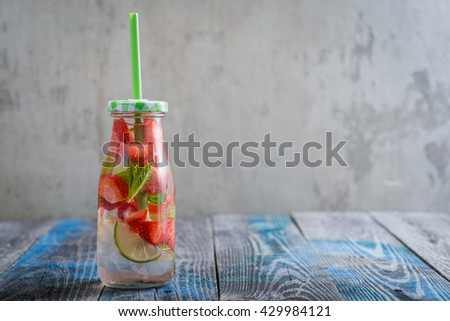 Bottle with lime and strawberry infused water on a rustic wooden table - stock photo