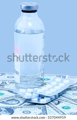 Bottle with medicine and tablets on the paper dollars in blue light