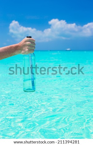 Bottle with message at the hand - stock photo